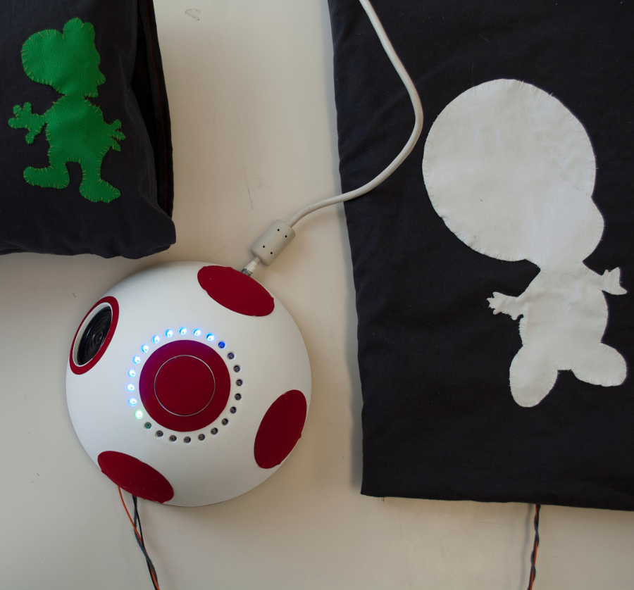 Photo of the Rattle Cushion alarm system with a pillow in the upper left (including a Yoshi silhouette) corner and a mat on the right (including a Toad silhouette).  In the middle the core alarm system in the form of a mushroom is shown.